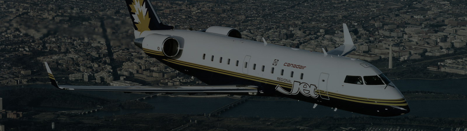 MHIRJ regional jet flying over a city